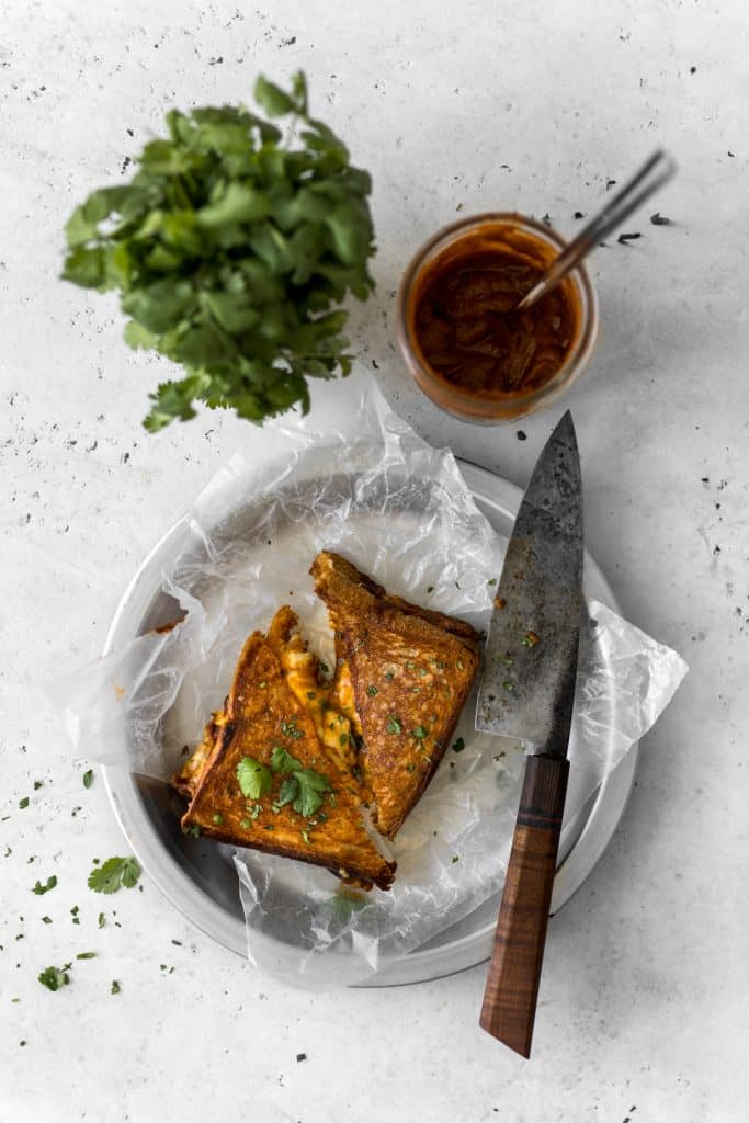 Grilled cheese next to a knife, butter chicken sauce, and cilantro