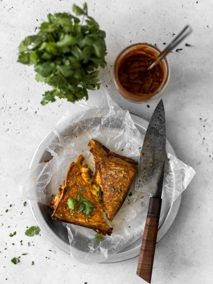 Butter Chicken Grilled Cheese with knife and cilantro