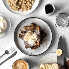 Cinnamon French Toast with whipped cream with sliced bananas, hazelnuts, coffee and maple syrup