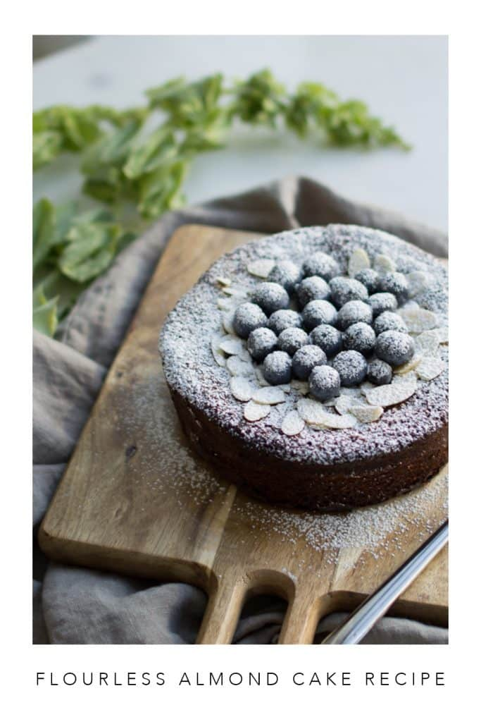 Flourless almond flour cake with blueberries on a wooden board.