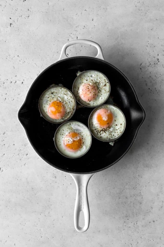 4 eggs in rings cooking on a cast iron skillet