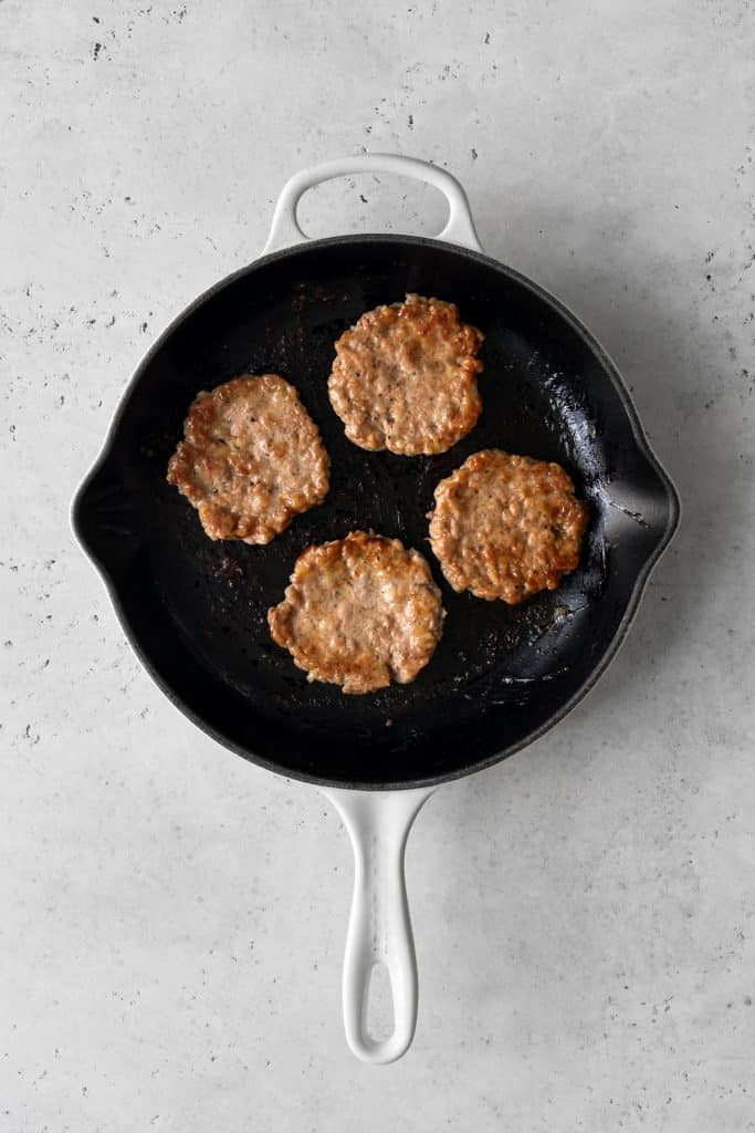 4 sausage patties cooking in a frying pan