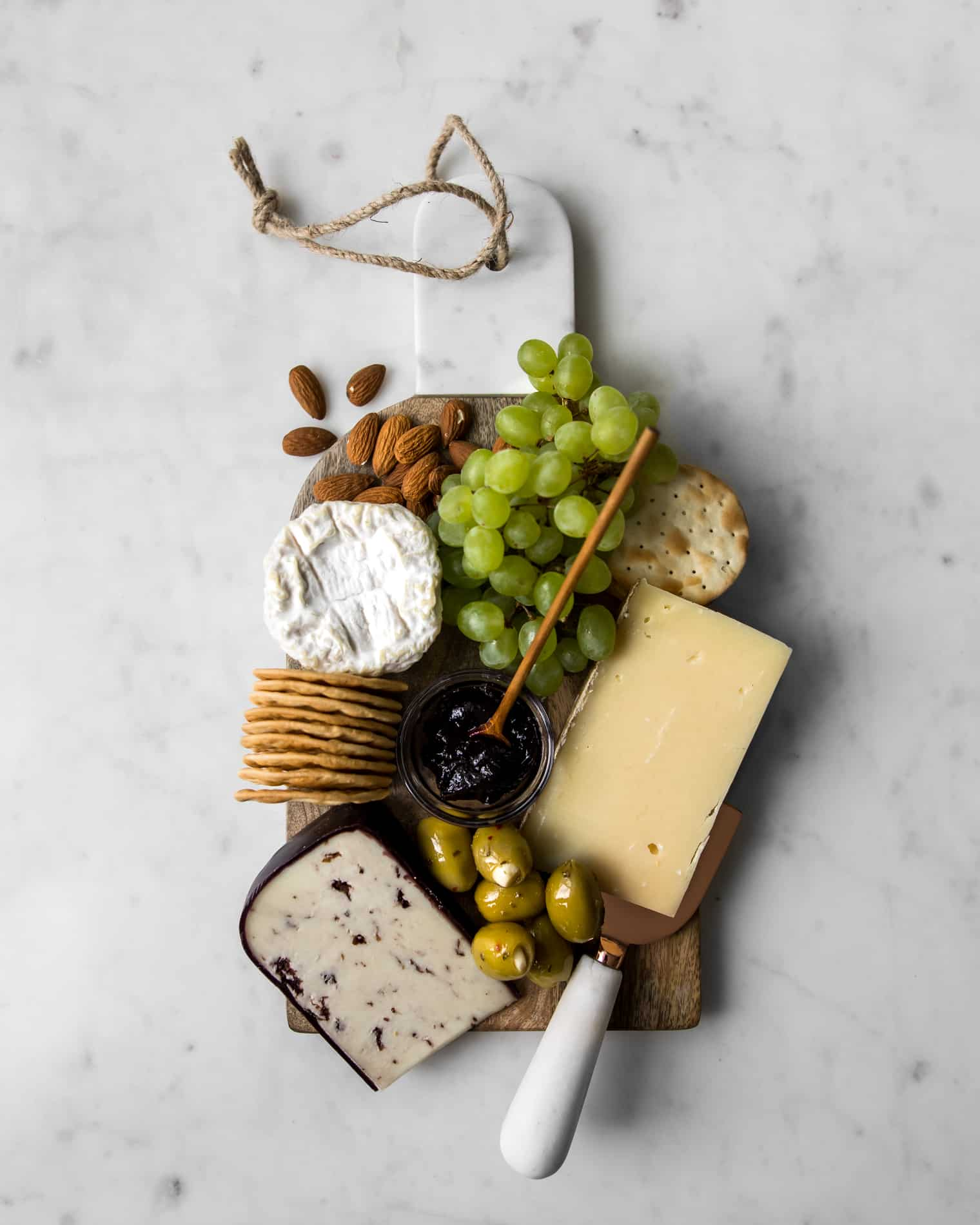 Flat lay of cheeseboard with grapes, three cheeses, almonds, grapes, olives and jelly