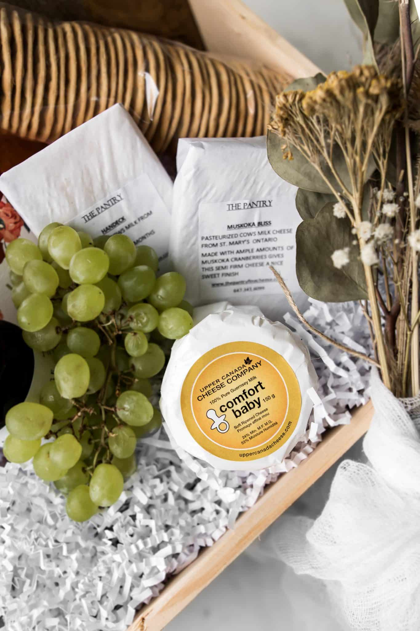 Close up of cheeses, dried flowers and grapes for a virtual baby shower gift box