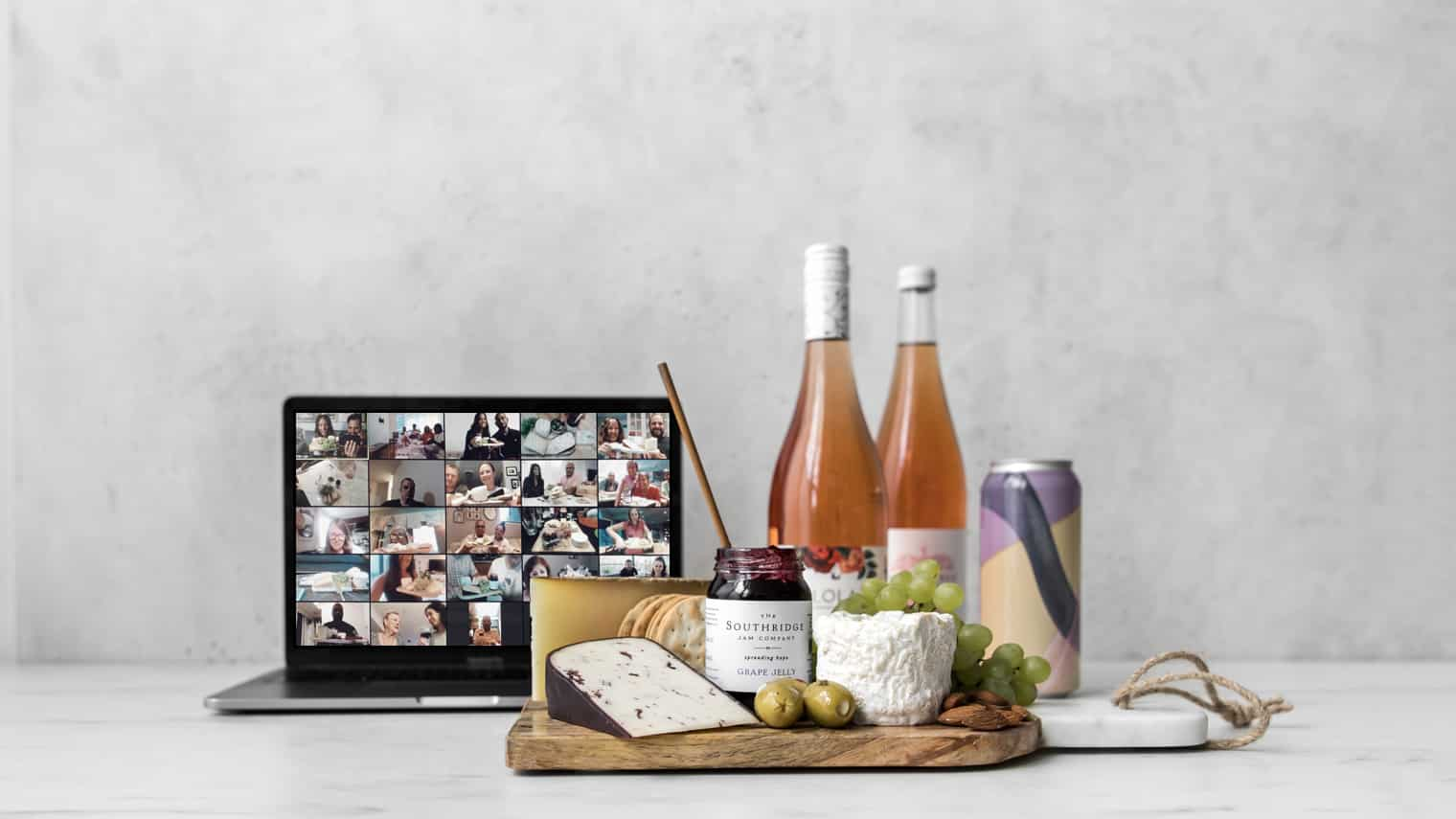 Computer, wine bottles and styled cheese board