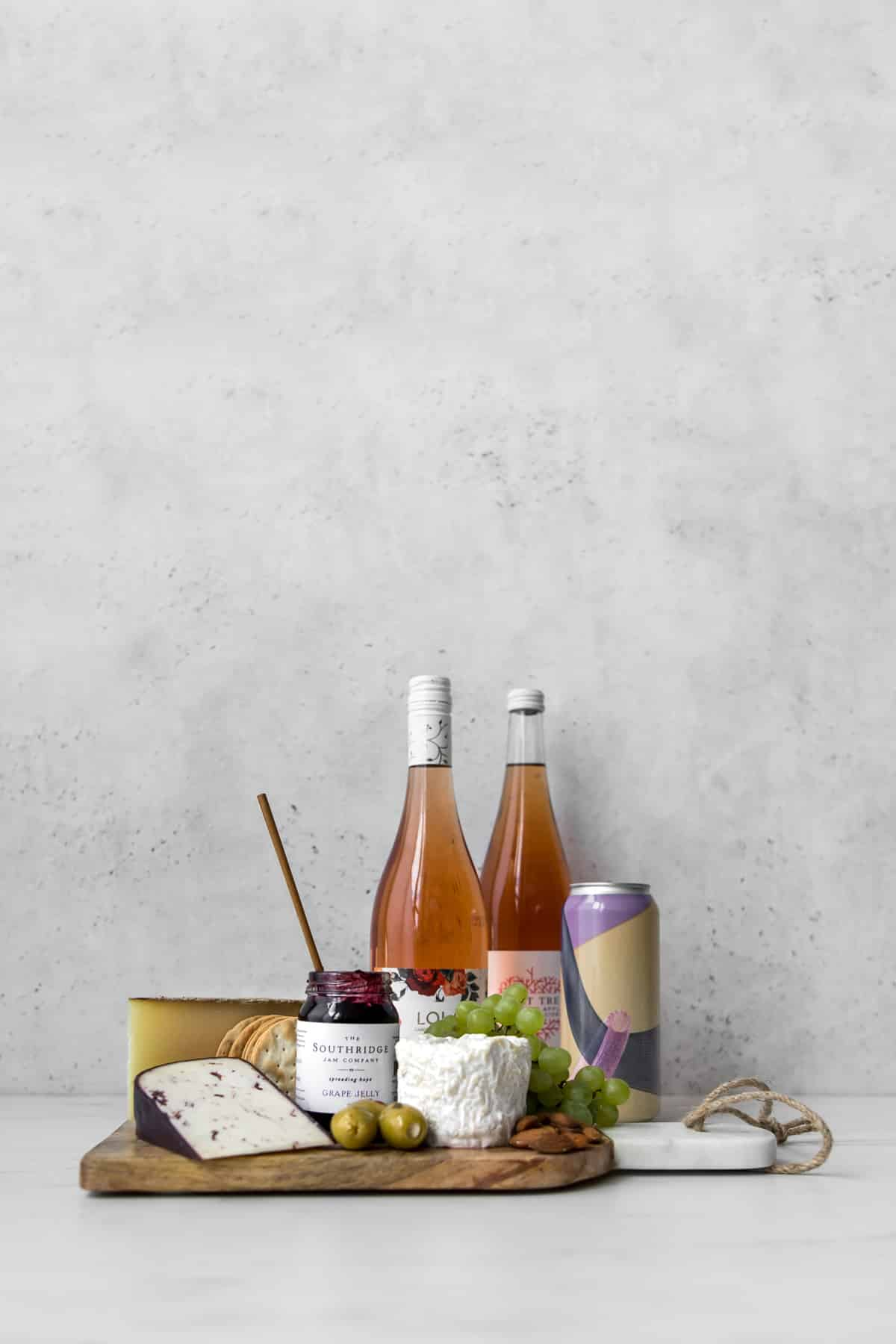 Wine, beer and cider bottles behind a cheeseboard