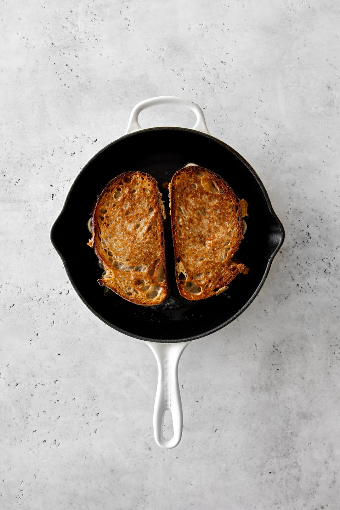 Two grilled cheese sandwiches cooking in a cast-iron skillet