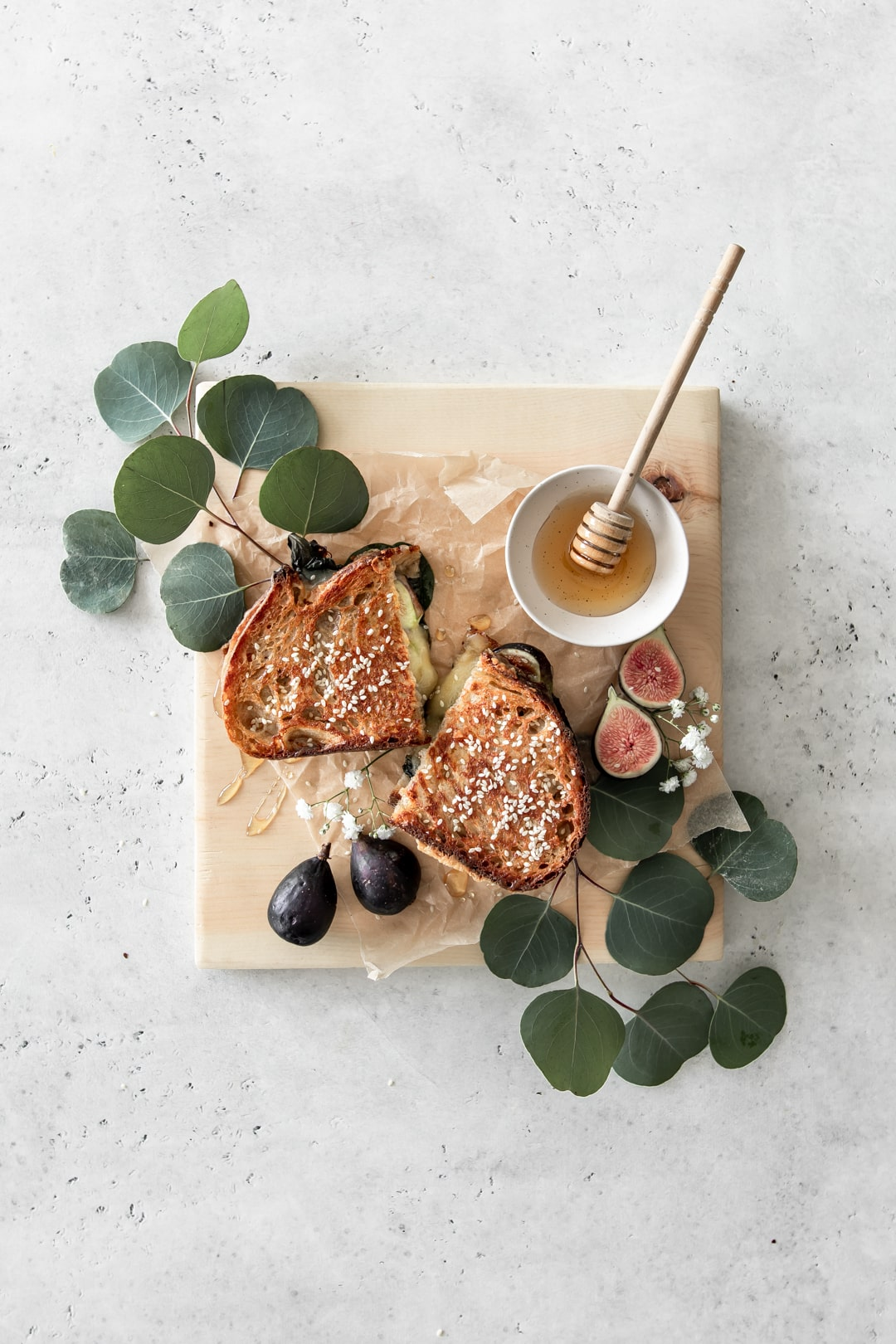 Gourmet grilled cheese halves on a wooden board with figs and honey.