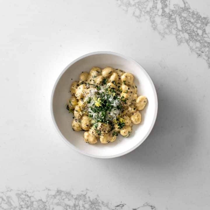 Bowl of gnocchi in cream sauce with basil, parmesan and lemon zest