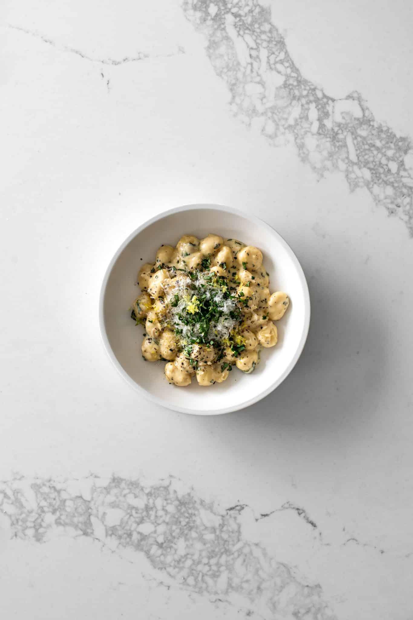 Bowl of one-pot gnocchi with lemon cream sauce with basil, parmesan and lemon zest
