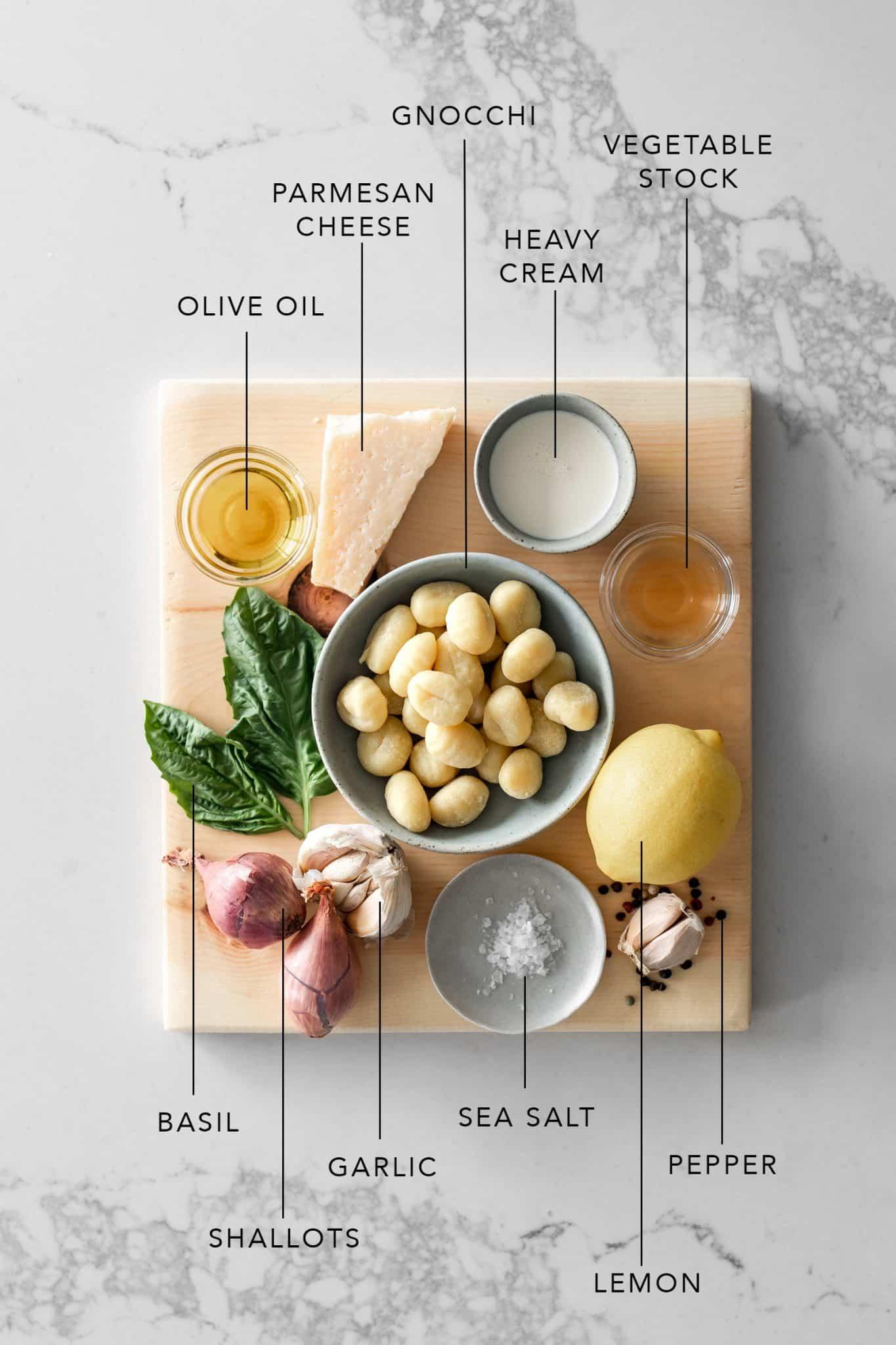 Wood board with olive oil, parmesan, gnocchi, cream, vegetable stock, basil, shallots, garlic, sea salt, lemon and peppercorns