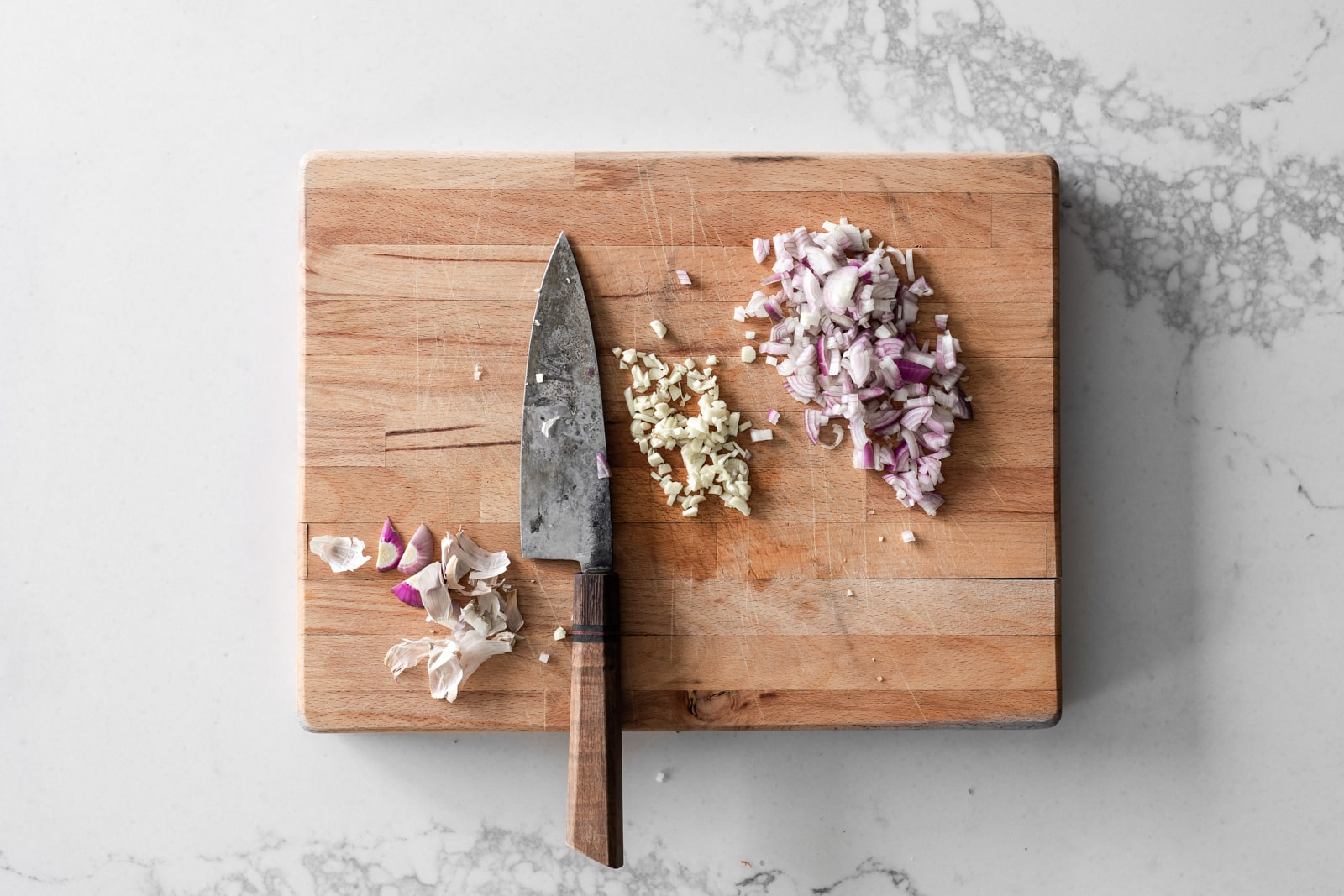 Wood Cutting Board with Knife, Chopped Shallots, Garlic and scraps