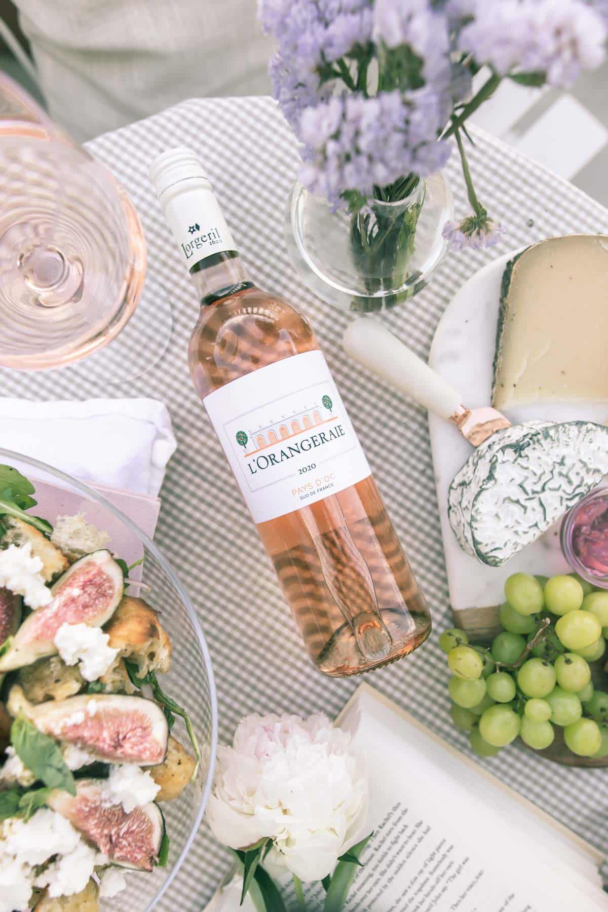 Bottle of L'orangeraie Rose surrounded by cheeseboard, flowers and salad.