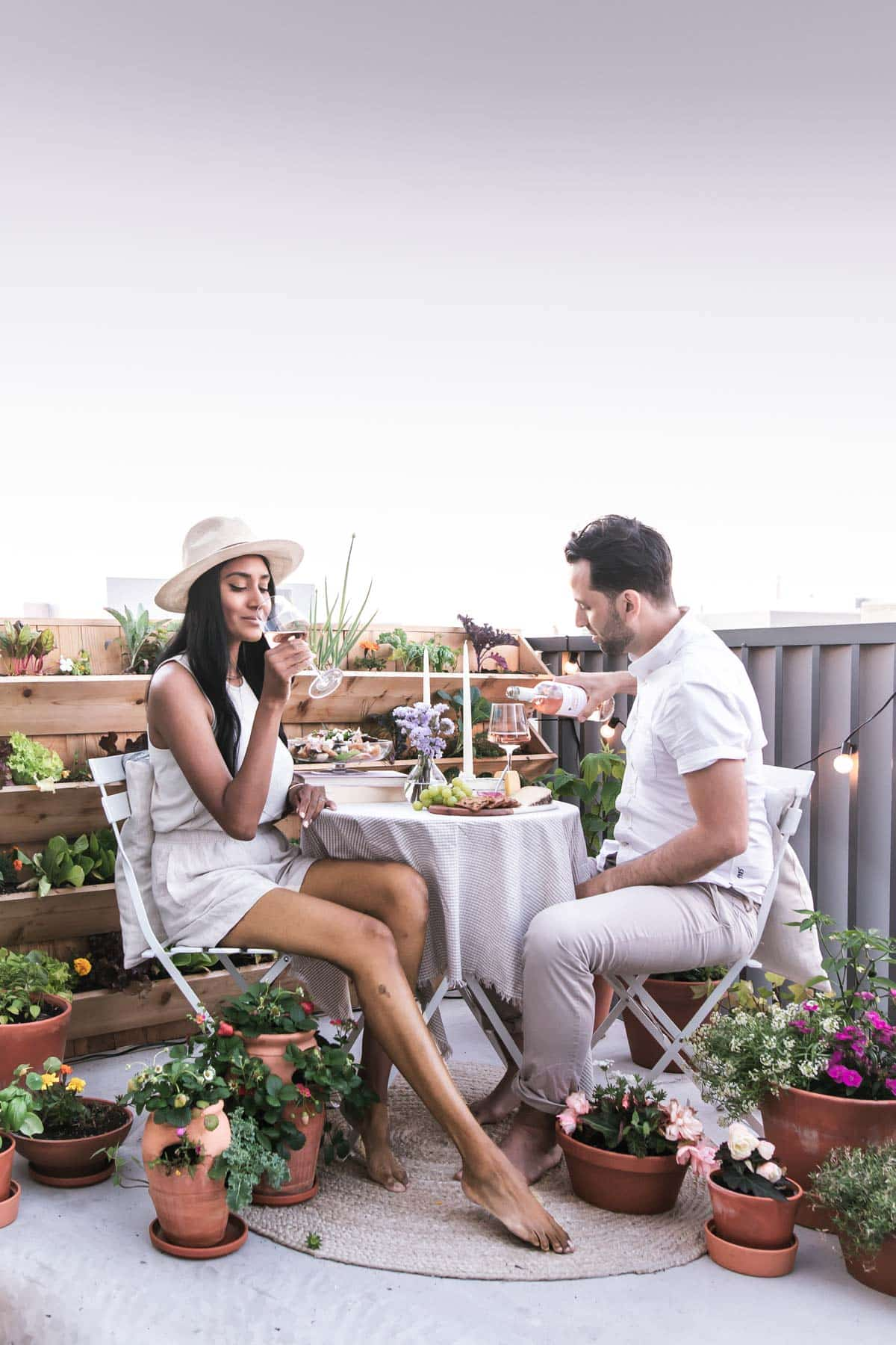 Mystique Mattai and Philip Lago enjoying rose wine in an al fresco dining setting surrounded by flowers in pots.