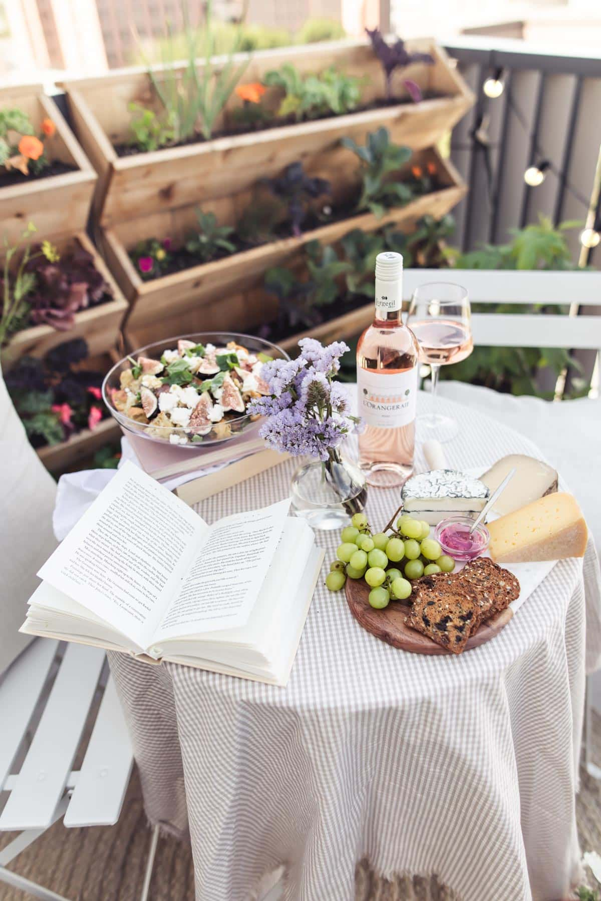 Bistro table with book, flowers, cheeseboard, rose wine and vertical planter in the background.