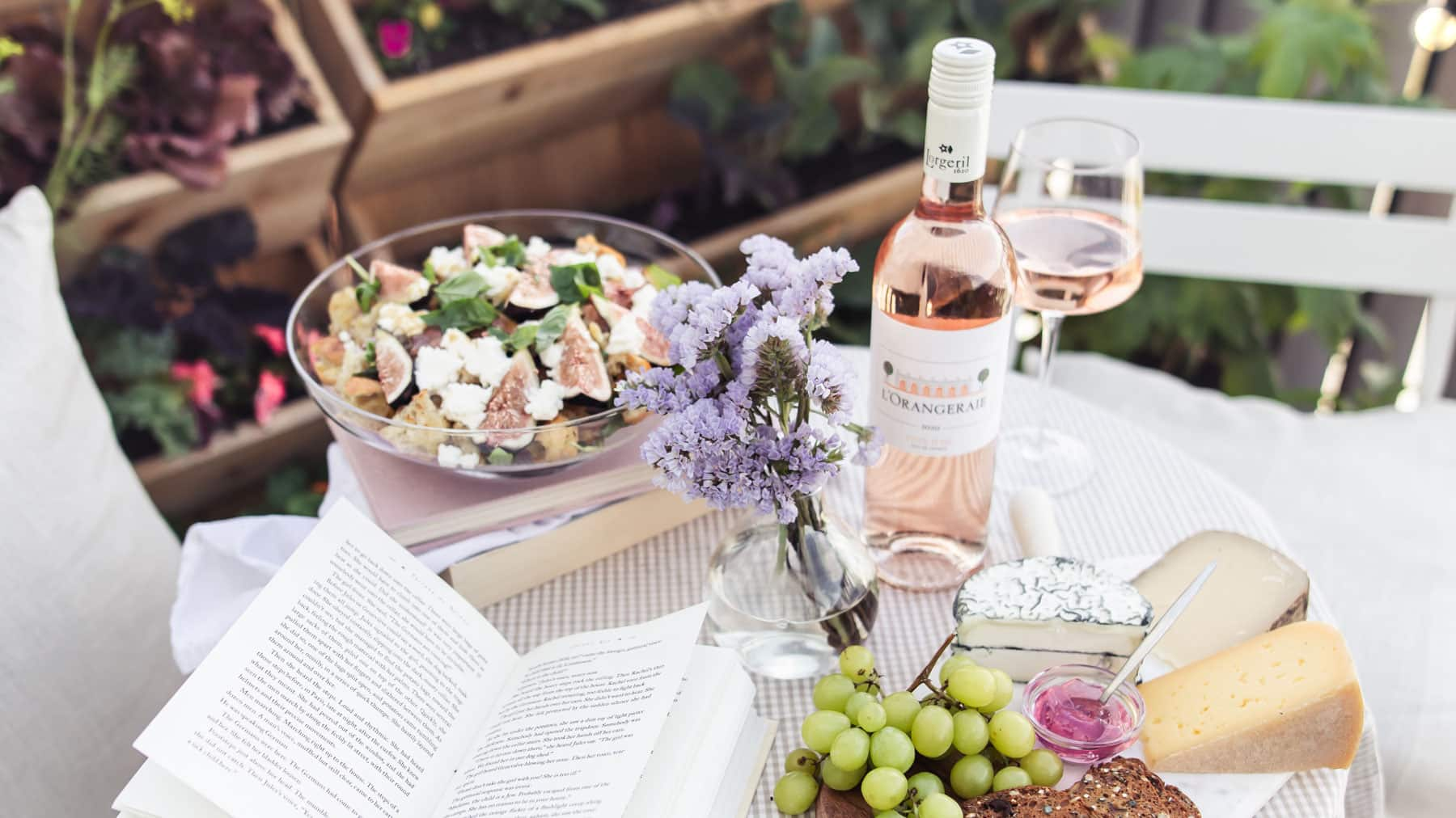 Bistro table with book, salad, cheeseboard, flowers and rose wine.