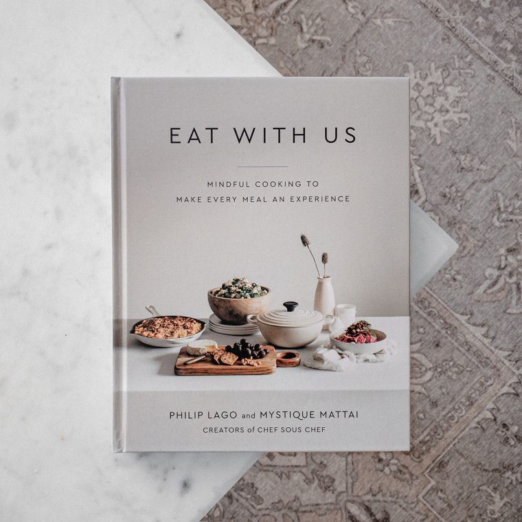 Eat With Us Cookbook on Marble Table with Patterned Background
