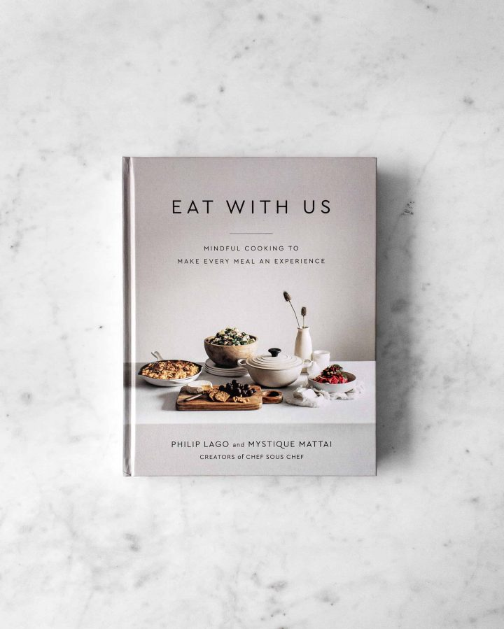 Eat With Us Cookbook on marble table