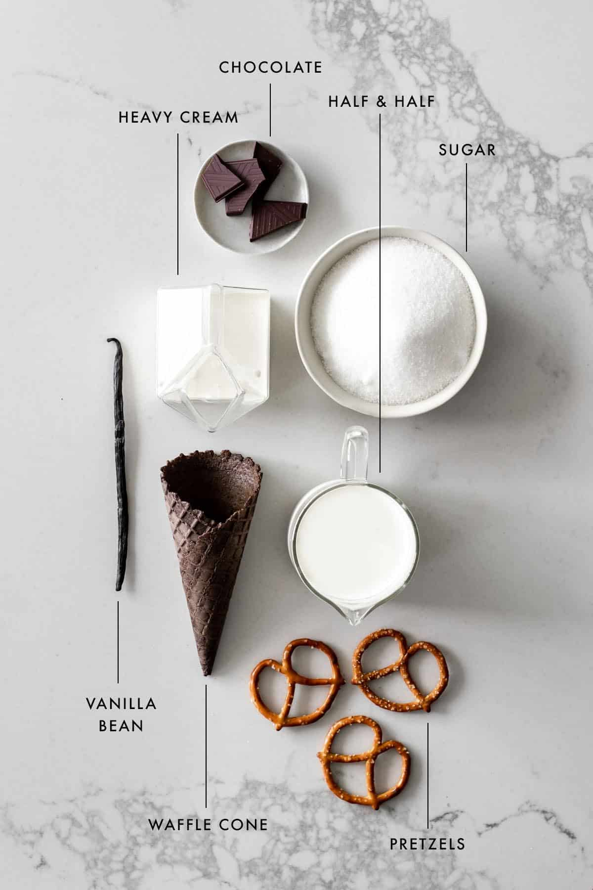 Flat lay of heavy cream, chocolate, half and half, sugar, vanilla bean, waffle cone, and pretzels.