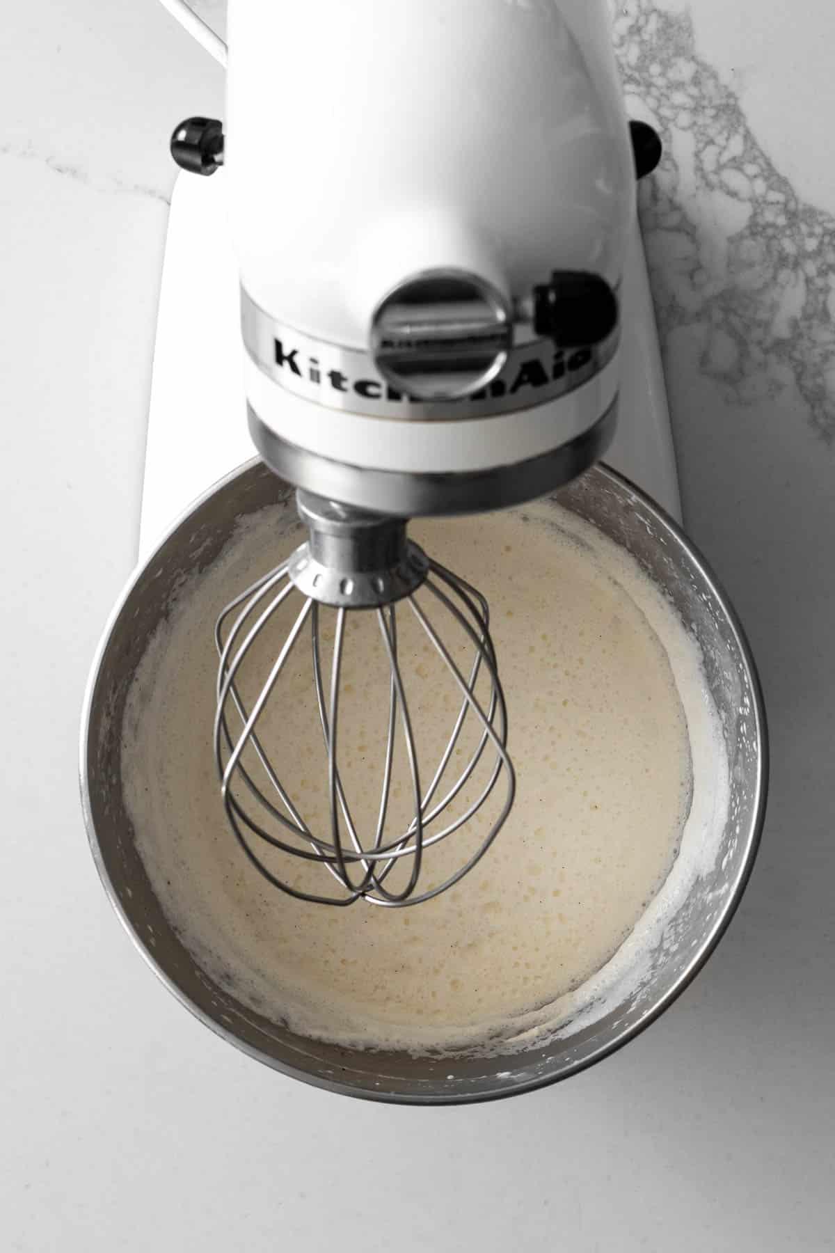 Partially frozen ice cream in a white kitchen-aid mixer