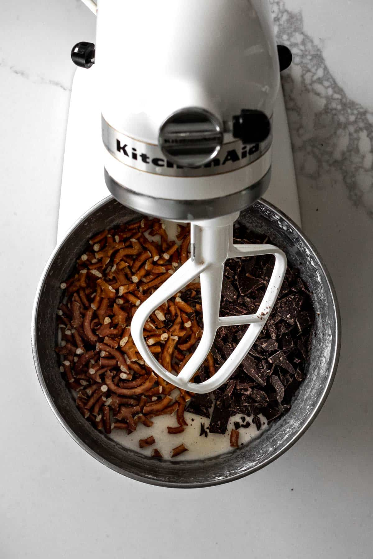 No churn ice cream in kitchen-aid mixer with pretzel and chocolate pieces