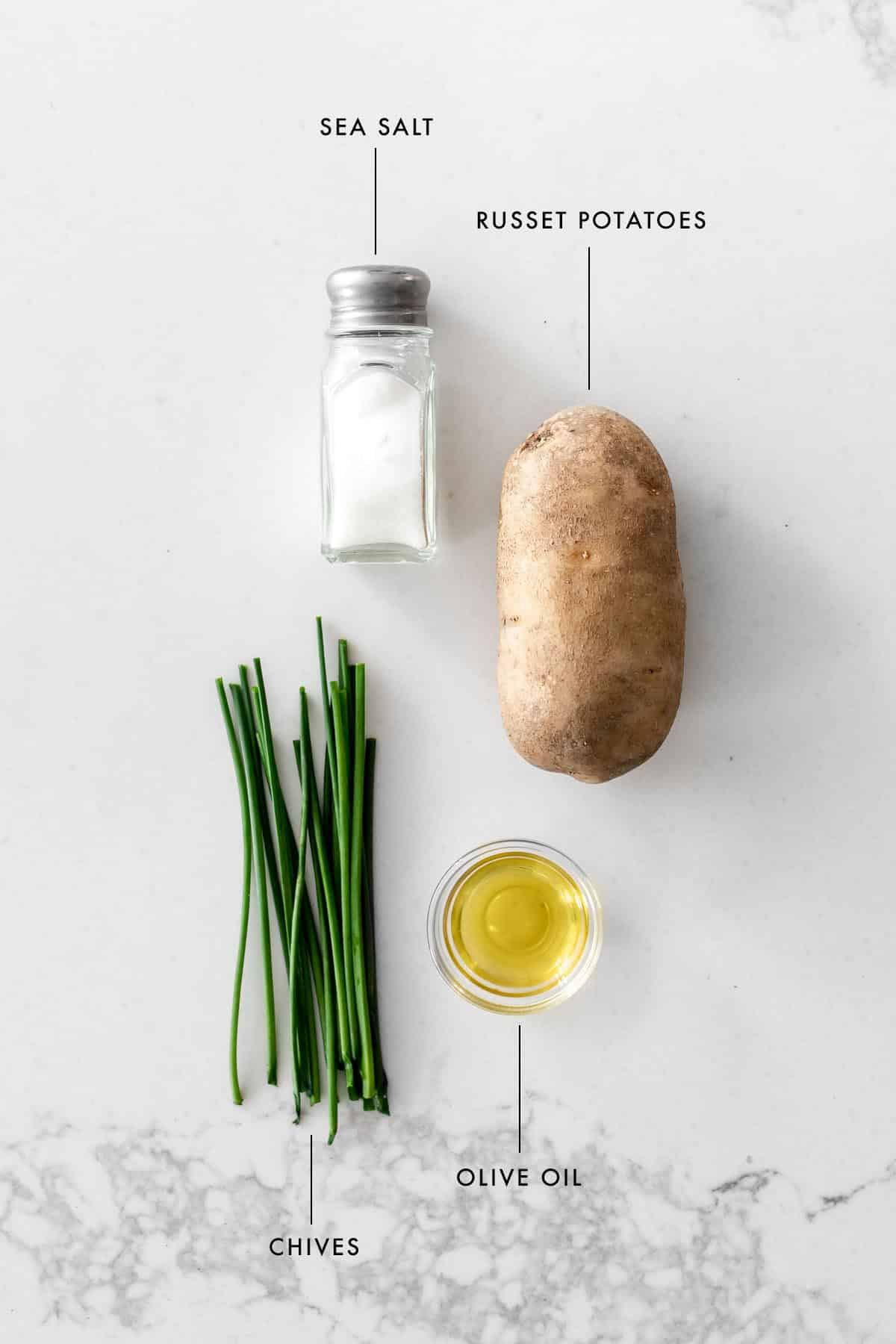 Salt shaker, russet potato, chives and olive oil flat lay with ingredient labels