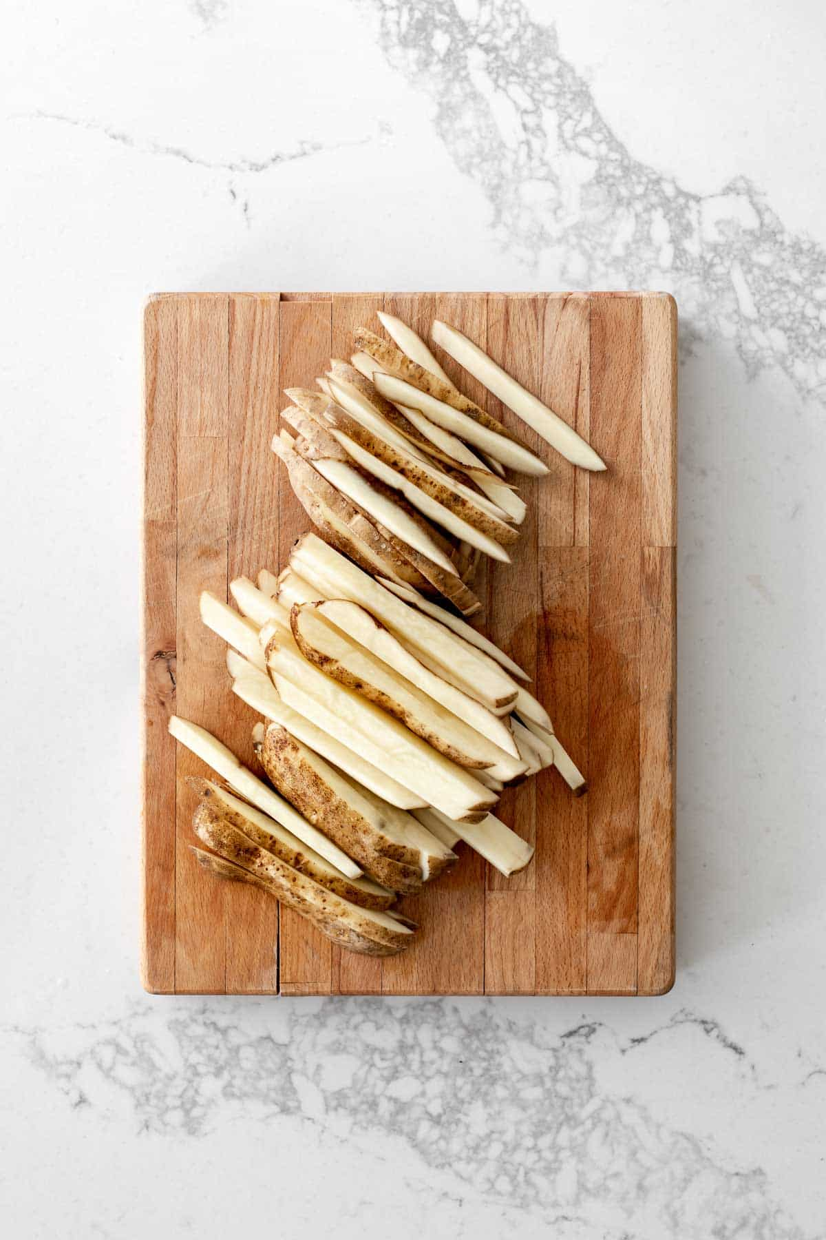 Potatoes cut into sticks on a wooden cutting board