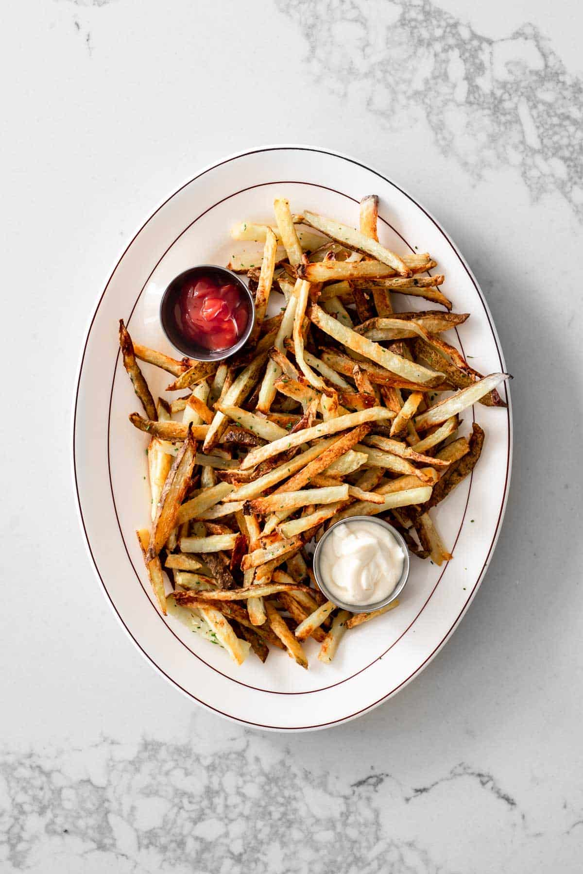 Oven baked french fries on a diner plate with ketchup and mayonnaise
