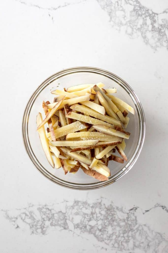 Boiled potato sticks in a bowl with olive oil and salt