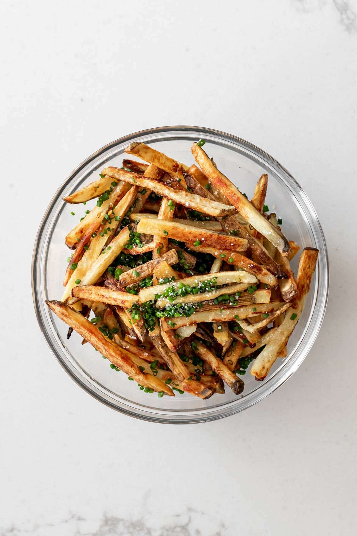 Crispy oven fries in a bowl with chives and salt