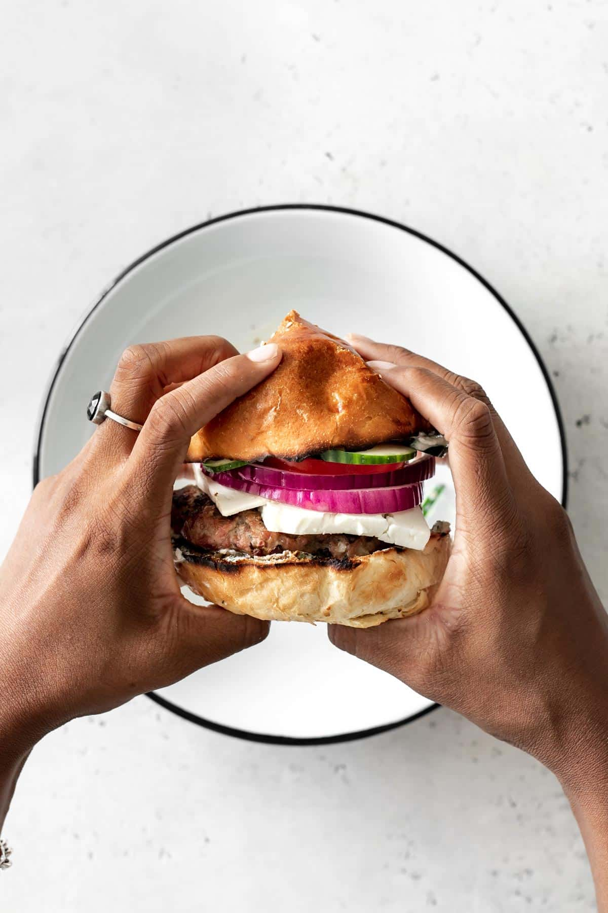 Hands holding a Turkey Burger over a white dish