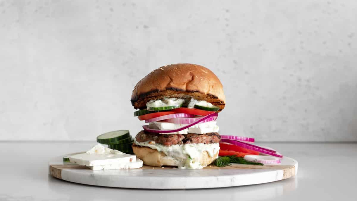 Turkey Burger on a bun with tzatziki sauce, feta cheese, red onion, tomato and cucumbers