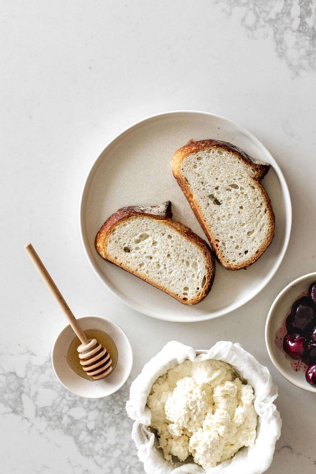 Bread on a plate with bowl of honey, bowl of ricotta cheese and bowl of cherries