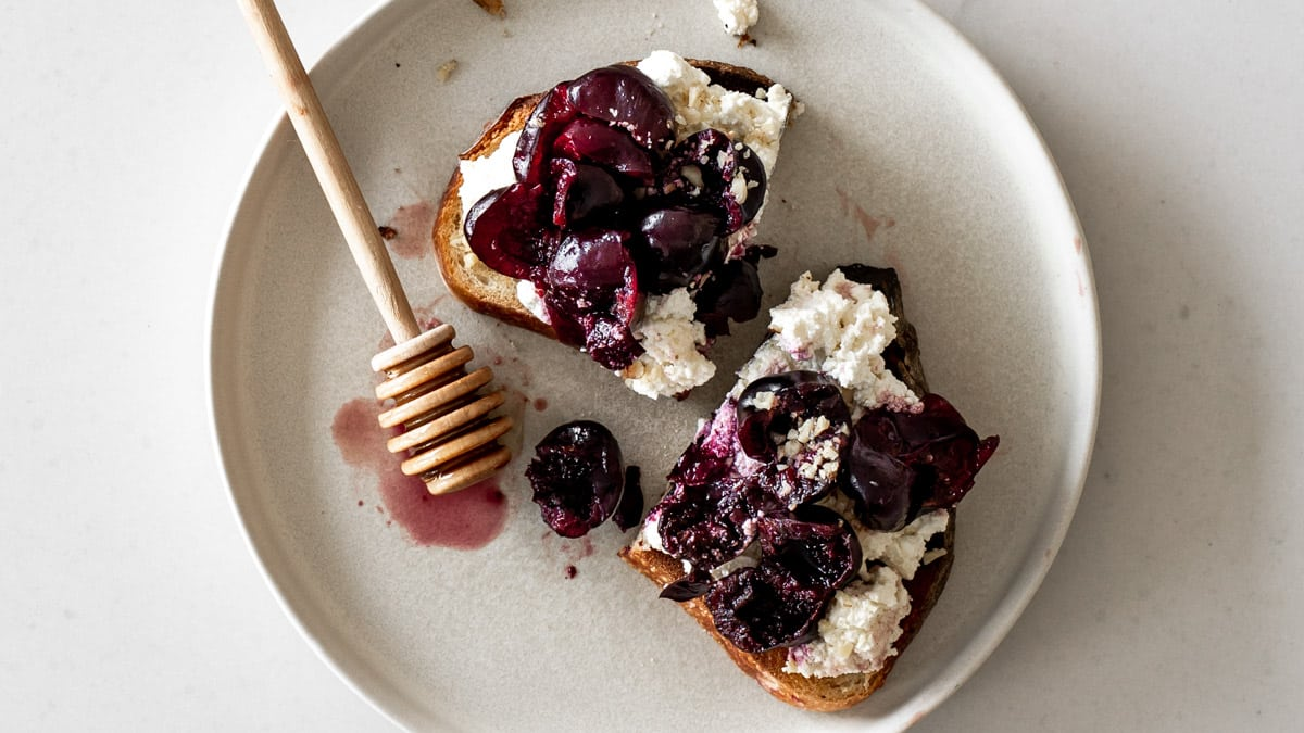 Ricotta Toast with Cherries on a plate with a honey dipper