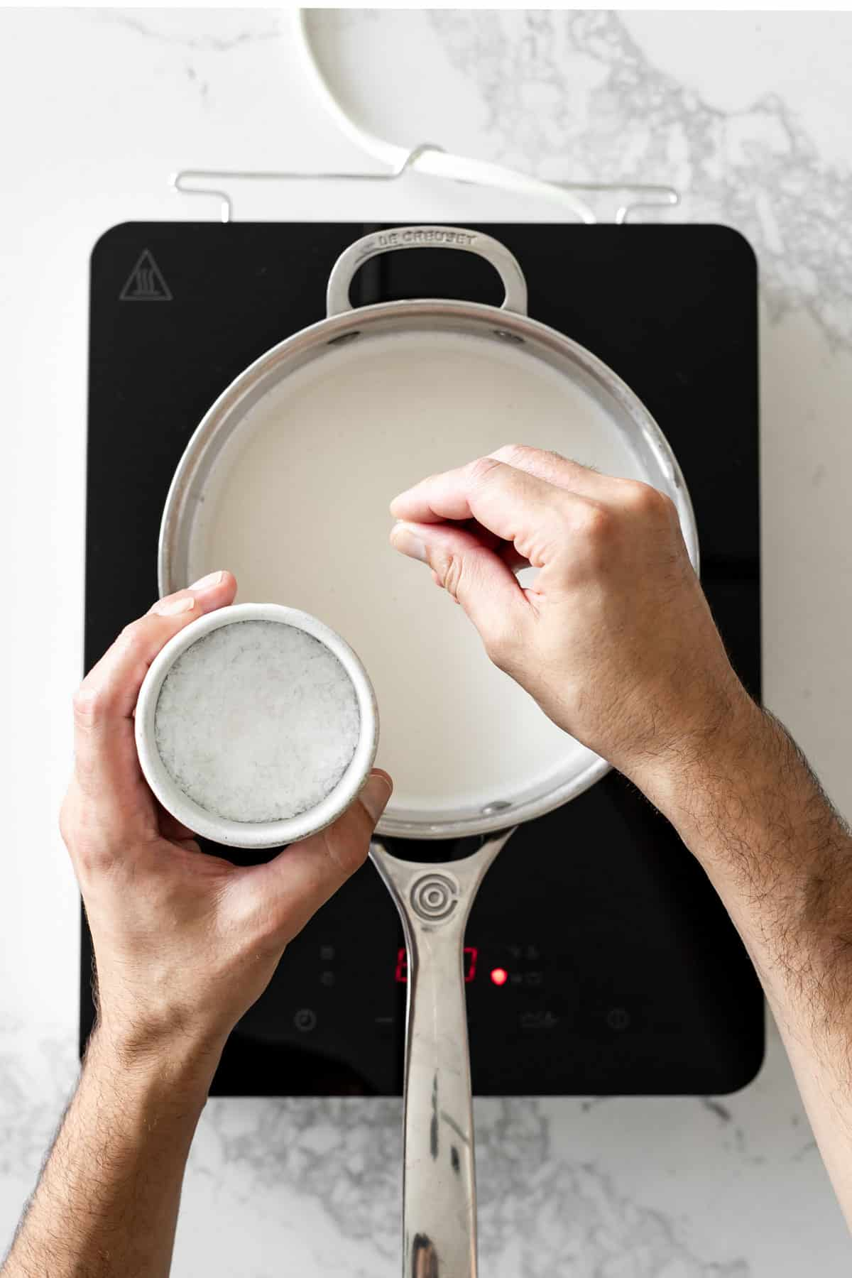 Hand sprinkling salt into a saucepan with milk in it