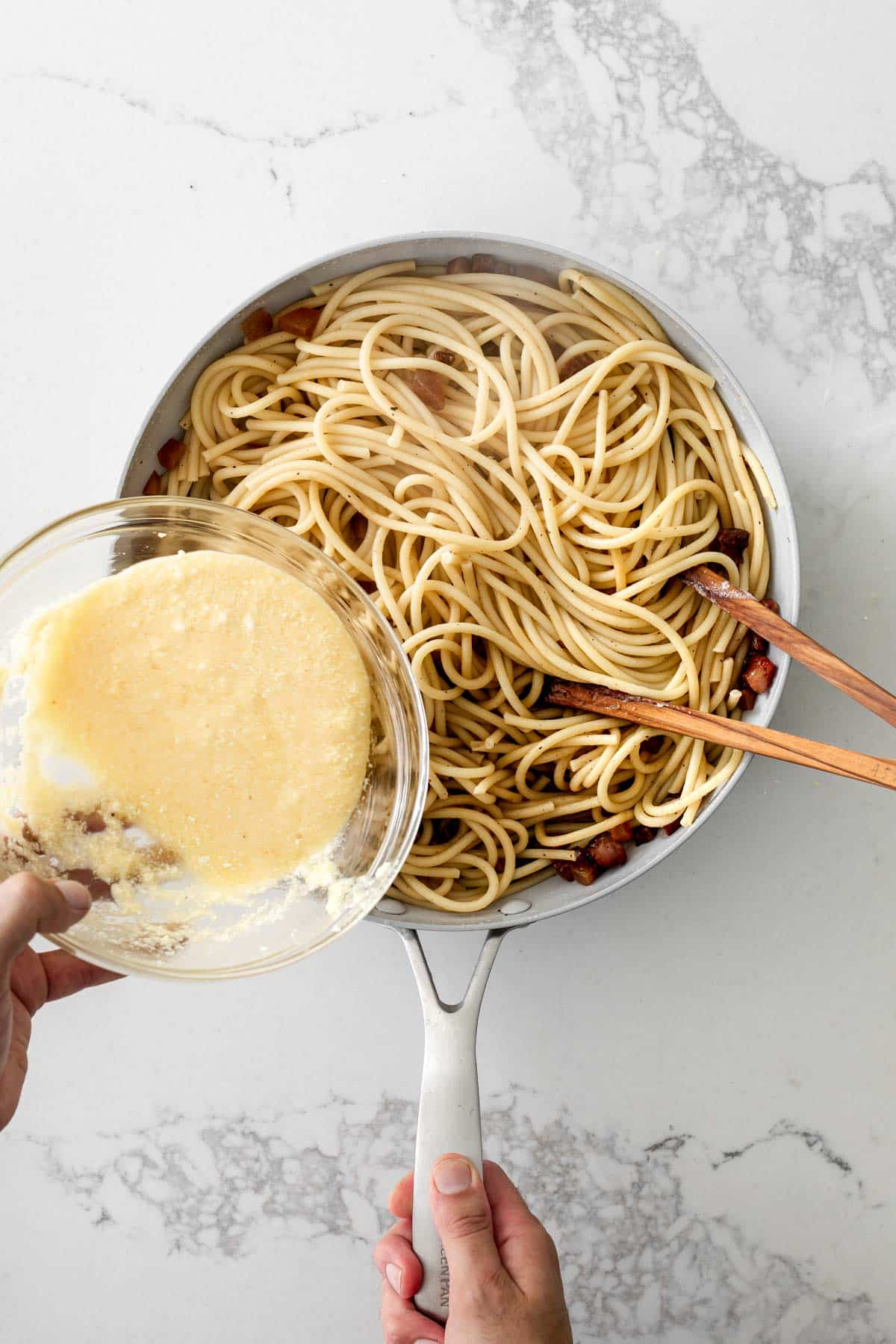 Hand holding a glass bowl with egg mixture above a pan of spaghetti and cubed guanciale
