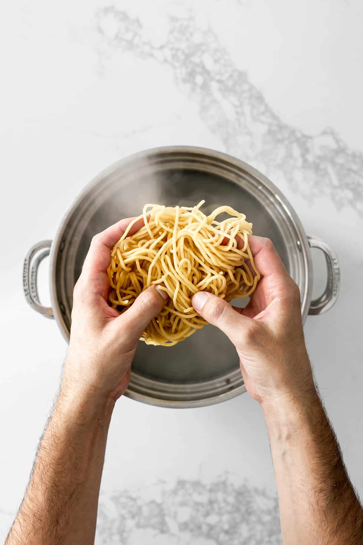 Hands holding fresh pasta above a pot of water