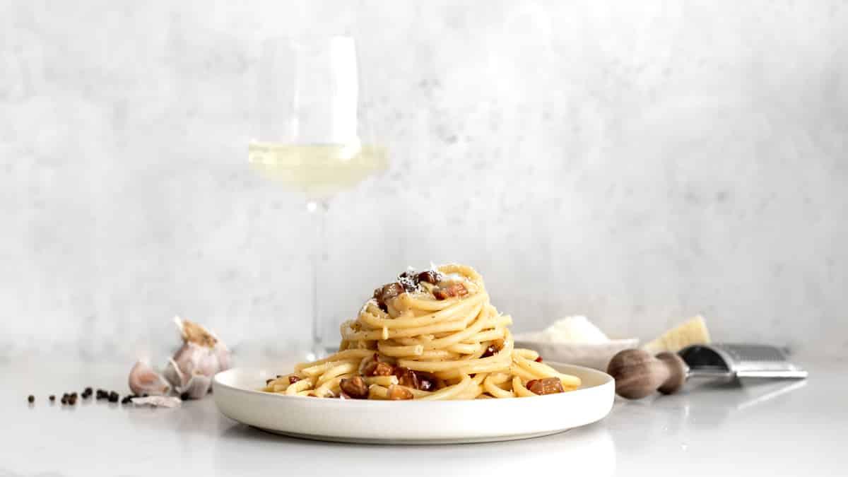 Side image of Spaghetti Carbonara, garlic, peppercorns, cheese grater, white wine and pecorino Romano