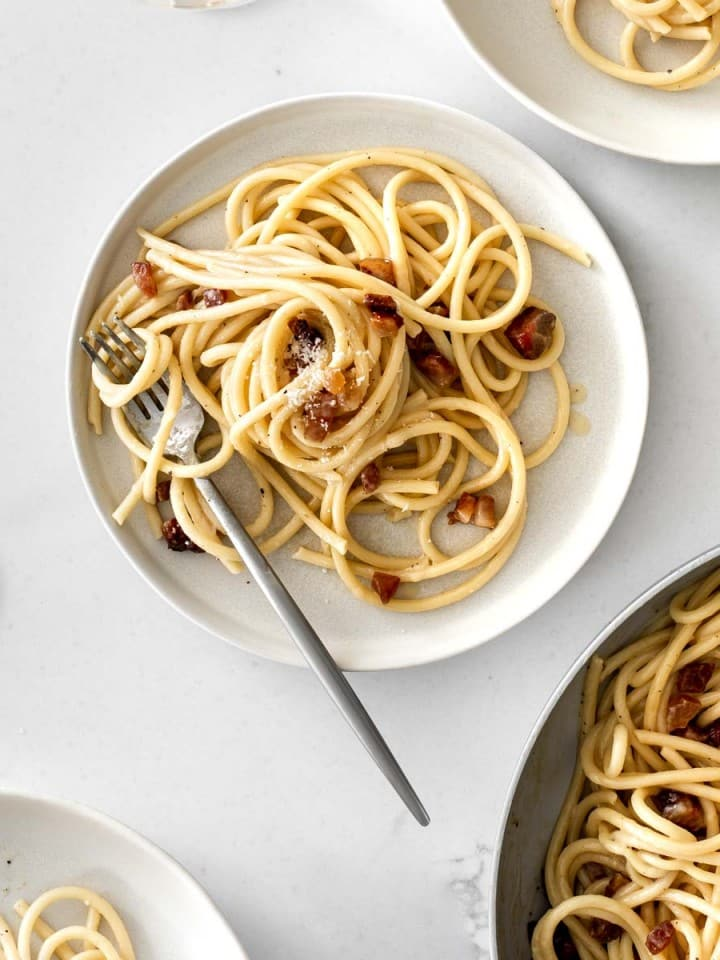 Plates of Spaghetti Carbonara and a glass of white wine
