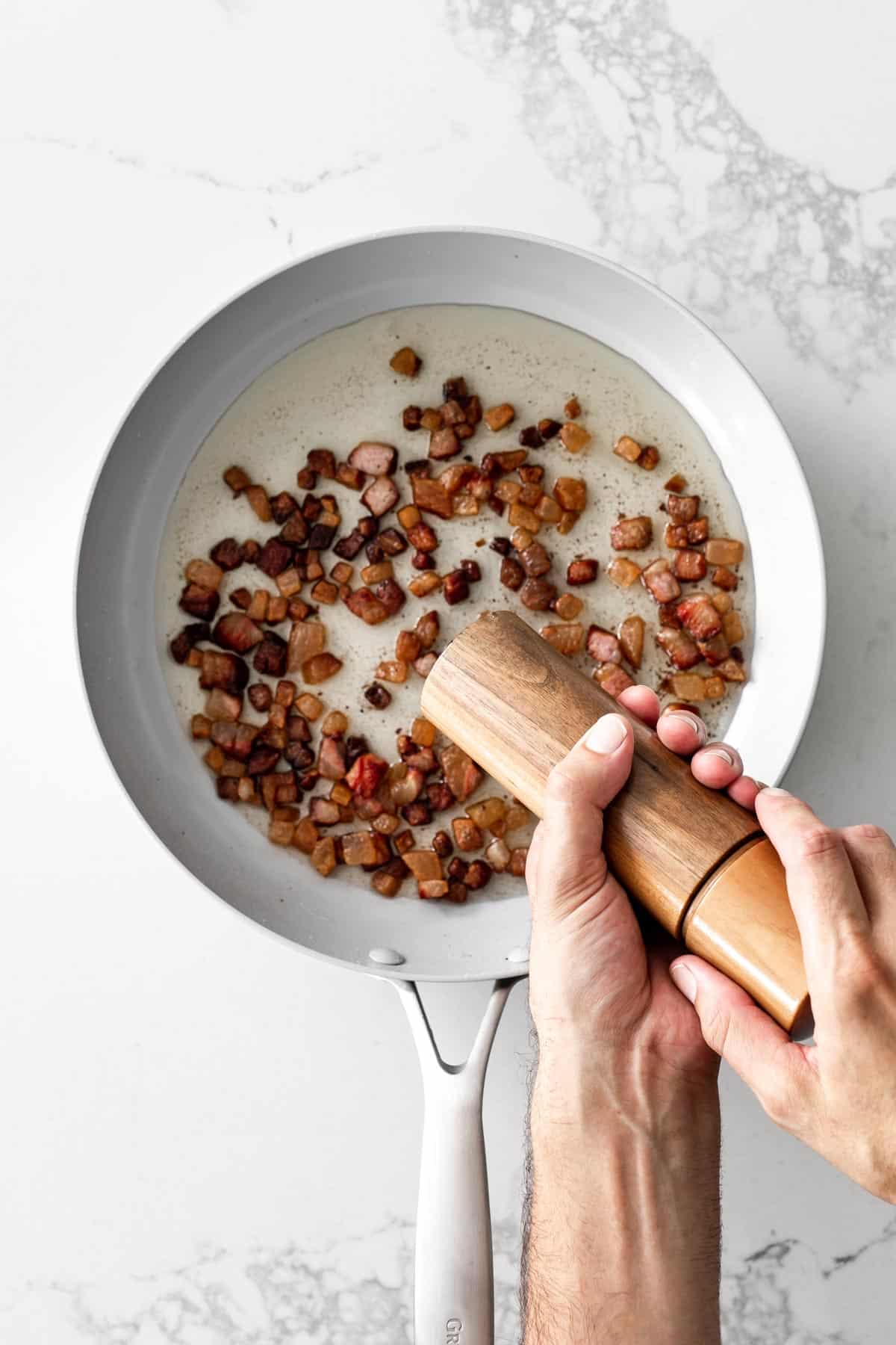 Hand grinding pepper into a pan with crispy pork