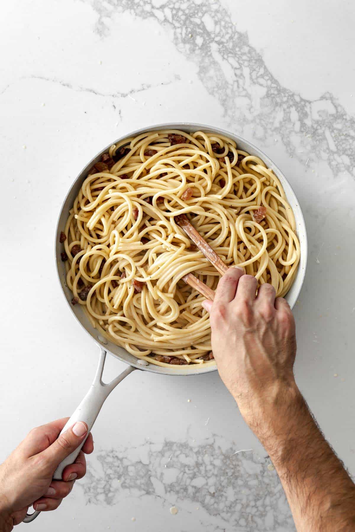 Hand holding tongs stirring spaghetti carbonara in a skillet