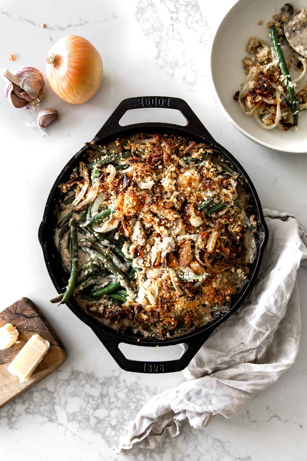 Green Bean Casserole in cast iron skillet with garlic, onions, parmesan and napkin placed around it