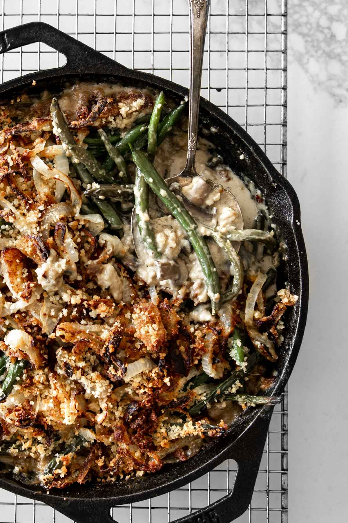 Close up of Green Bean Casserole in black skillet with antique spoon