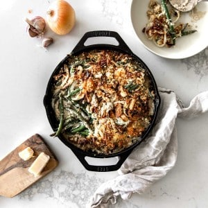 Green Bean Casserole in a Lodge Skillet with garlic, onion, parmesan and napkin around it