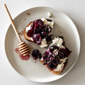 Cherry Ricotta Toast on a plate with honey stick